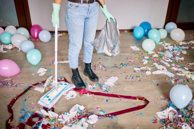 Mulher com vassoura limpando a bagunça do chão do quarto depois dos confetes da festa