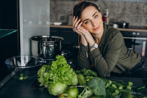 Mulher com vegetais verdes na cozinha