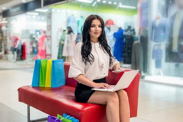 Mulher com ventilador de dólar e laptop sentada no shopping