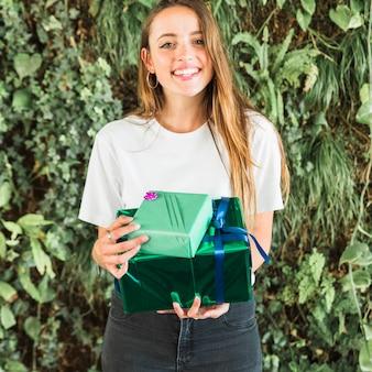 Mulher, com, verde, caixas presente, olhando câmera