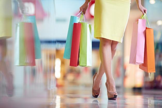 Mulher com vestido amarelo e sacos de compras