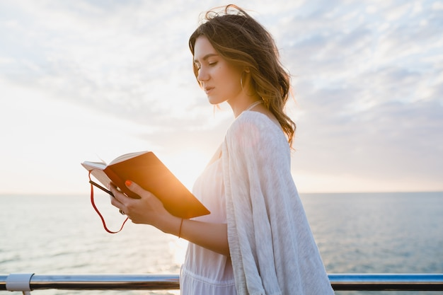 Mulher com vestido branco de verão caminhando à beira-mar ao nascer do sol com livro diário em clima romântico pensando e fazendo anotações