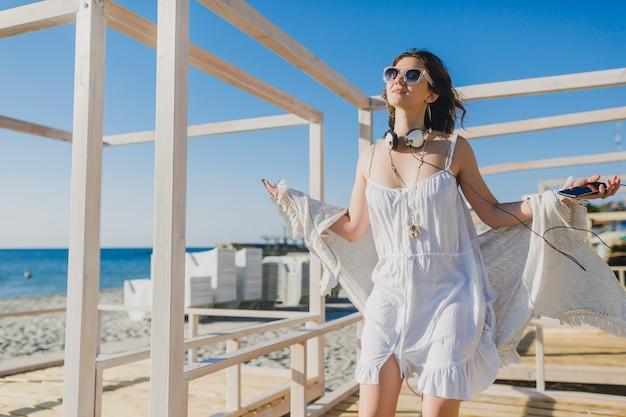 Mulher com vestido branco de verão ouvindo música em fones de ouvido, dançando e se divertindo