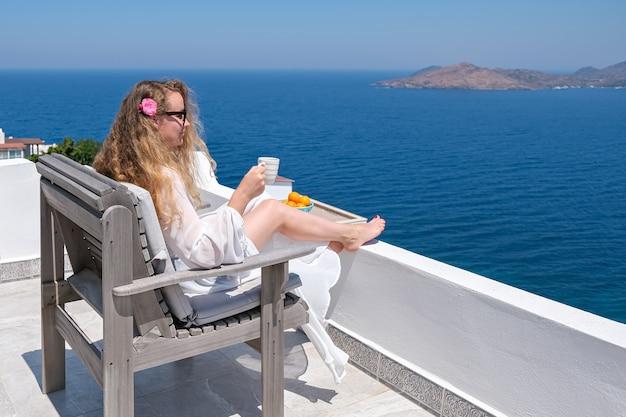 Mulher com vestido branco flor no cabelo e xícara de café no terraço