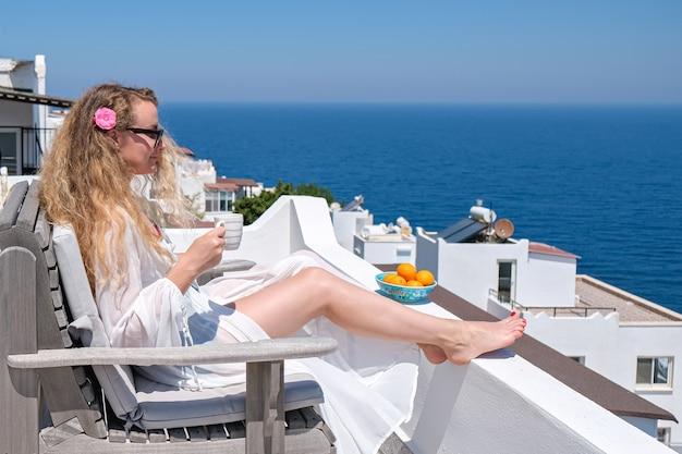 Mulher com vestido branco flor no cabelo e xícara de café sentada no terraço branco