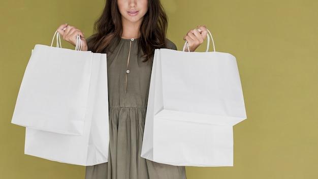 Mulher com vestido cáqui, segurando redes de compras