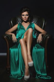 Mulher com vestido de seda verde lindo está posando no sofá de couro