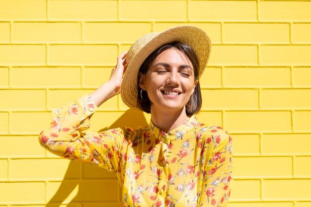 Mulher com vestido de verão amarelo e chapéu na parede de tijolo amarelo calma e positiva, gosta de dias ensolarados de verão
