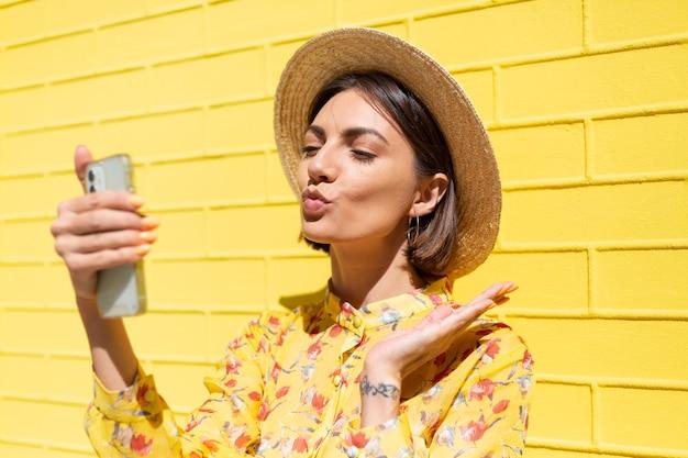 Mulher com vestido de verão amarelo e chapéu na parede de tijolo amarelo calmo e positivo segurando o telefone celular