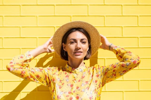 Mulher com vestido de verão amarelo e chapéu na parede de tijolo amarelo calmo e positivo
