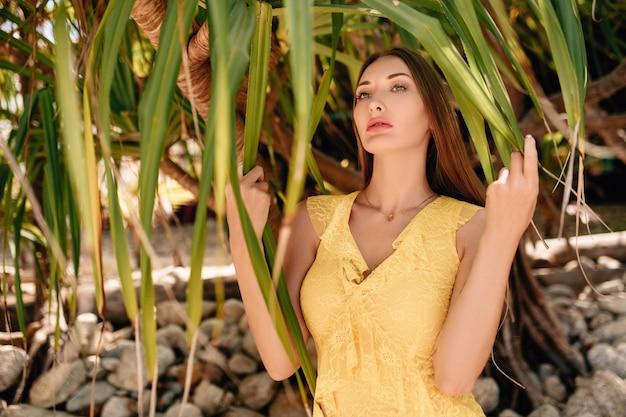Mulher com vestido de verão amarelo em pé perto de uma palmeira