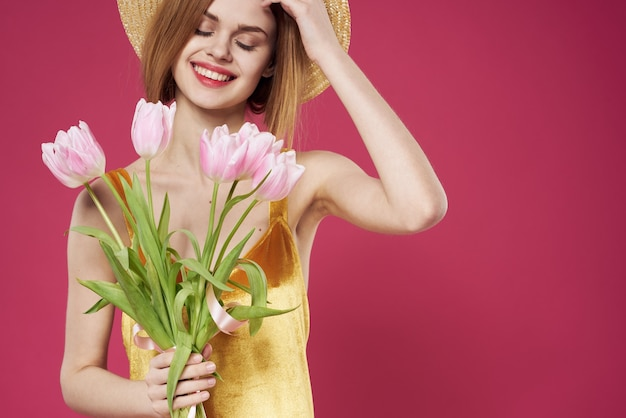 Mulher com vestido dourado buquê de flores presente feriado fundo rosa