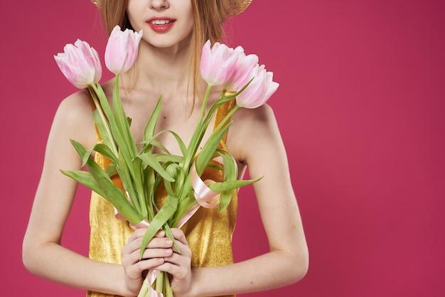 Mulher com vestido dourado buquê de flores presente feriado rosa