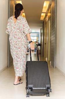 Mulher com vestido longo, andando com bagagem em um corredor de hotel.