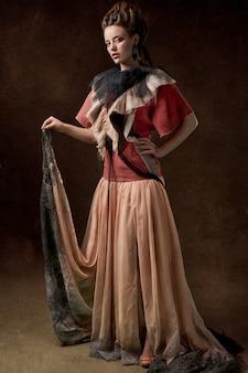 Mulher com vestido longo vermelho e rosa
