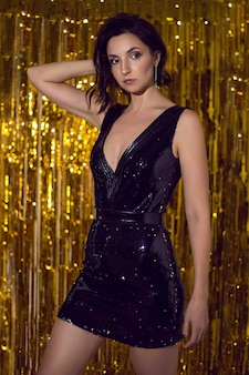 Mulher com vestido preto brilhante feito de brilhos está no estúdio em um fundo de ouropel dourado em comemoração