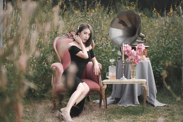 Mulher com vestido preto, sentada no sofá no jardim de flores com gramofone vintage e decoração.