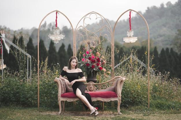 Mulher com vestido preto, sentada no sofá no jardim de flores.