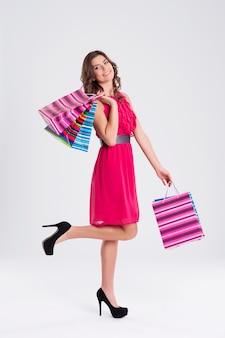 Mulher com vestido rosa segurando sacolas de compras