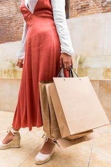 Mulher com vestido segurando sacola de compras