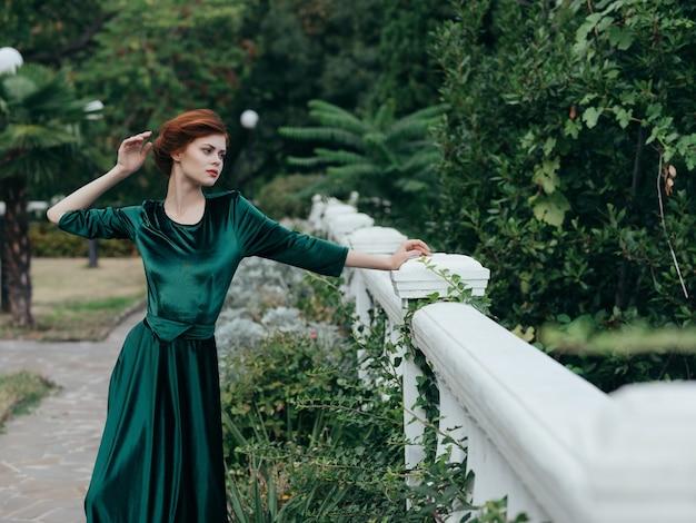 Mulher com vestido verde glamour romance passeio no parque