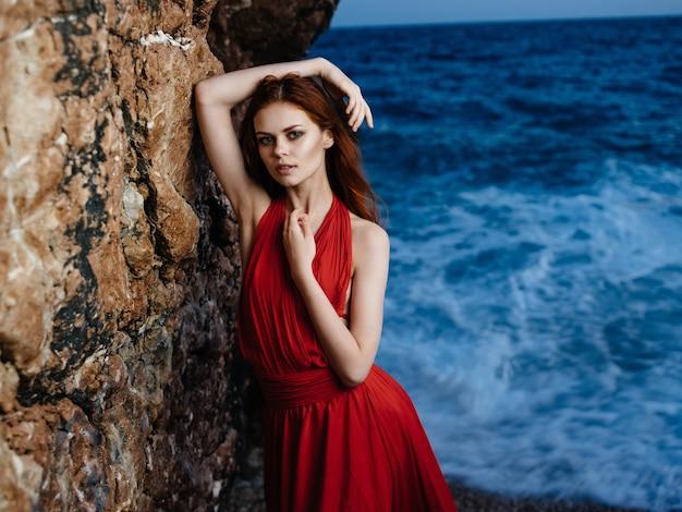 Mulher com vestido vermelho na costa dos oceanos posando silhueta da moda