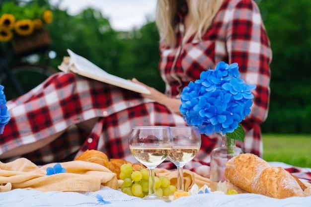 Mulher com vestido xadrez vermelho e chapéu sentada na manta de piquenique de malha branca lendo livro e bebendo vinho