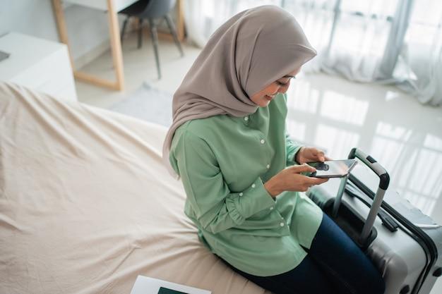 Mulher com véu sentada na cama segurando seu smartphone e mala