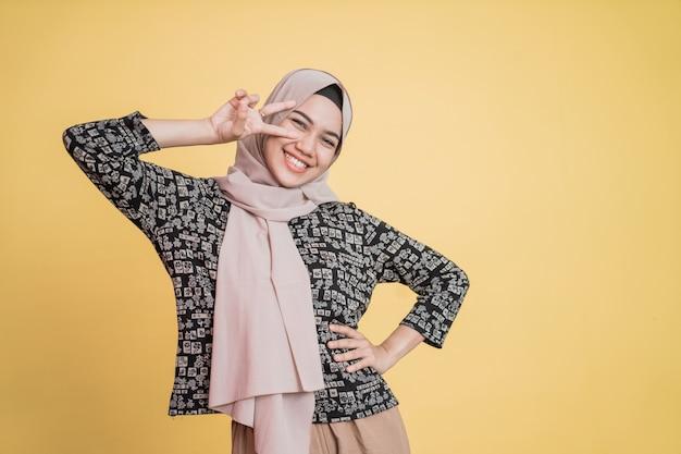 Mulher com véu sorrindo em paz fazendo gesto com os dois dedos com copyspace