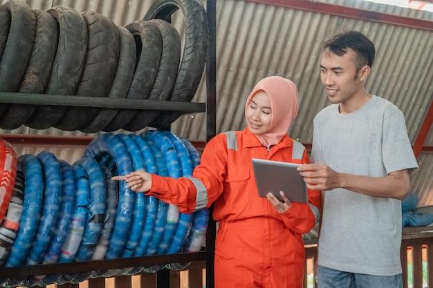 Mulher com véu usando um wearpack com uniforme apontando o dedo mostra o tipo de pneu na prateleira para os consumidores enquanto segura um tablet digital em uma oficina