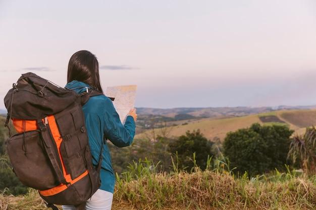 Mulher, com, viagem, mochila, olhando dentro mapa