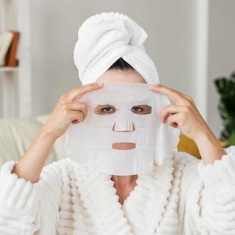 Mulher com visão frontal aplicando máscara facial