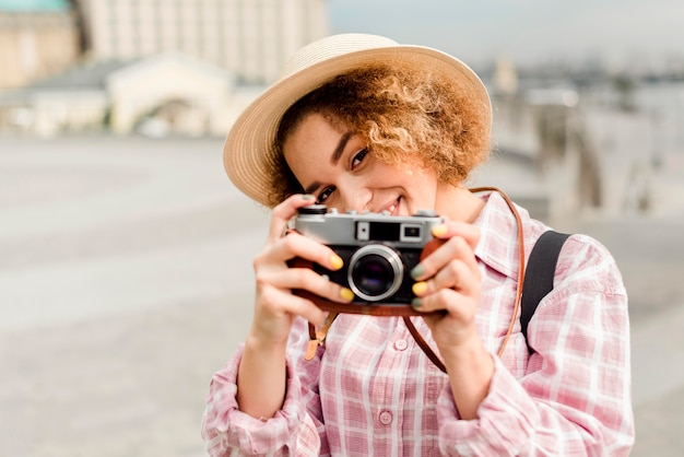 Mulher com visão frontal tirando uma foto com uma câmera enquanto viaja