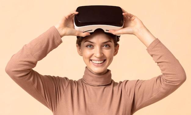 Mulher com visão frontal tocando fone de ouvido de realidade virtual