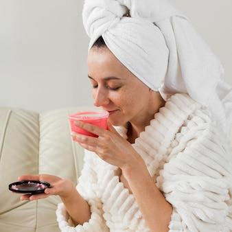 Mulher com visão lateral cheirando um creme