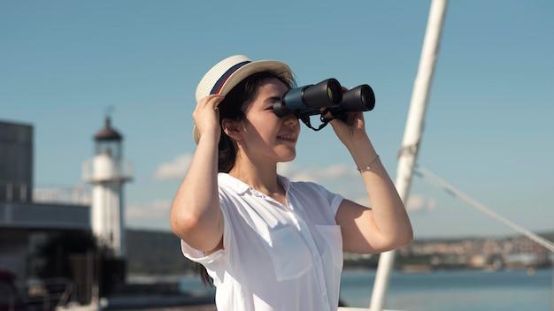 Mulher com visão lateral olhando através de binóculos