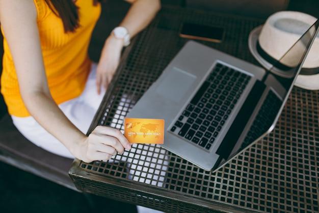 Mulher com vista de cima em um café de rua ao ar livre, sentada à mesa de ferro com um computador laptop pc, chapéu, segura na mão o cartão de crédito do banco