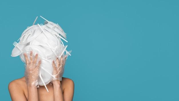 Mulher com vista frontal coberta com talheres de plástico branco