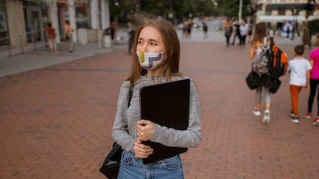 Mulher com vista frontal com máscara médica segurando seu laptop do lado de fora