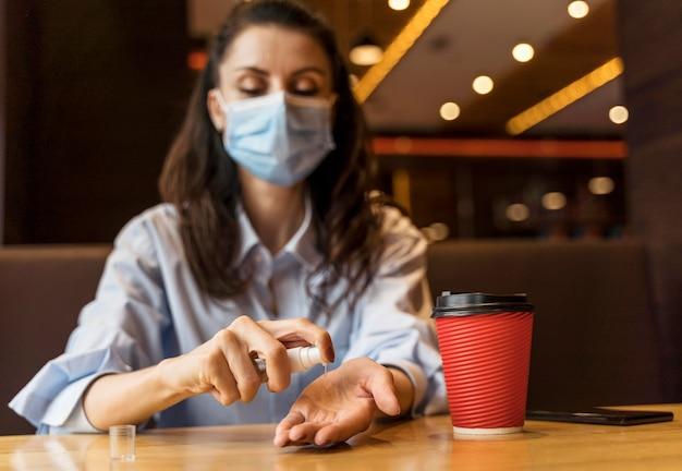 Mulher com vista frontal desinfetando as mãos em um restaurante
