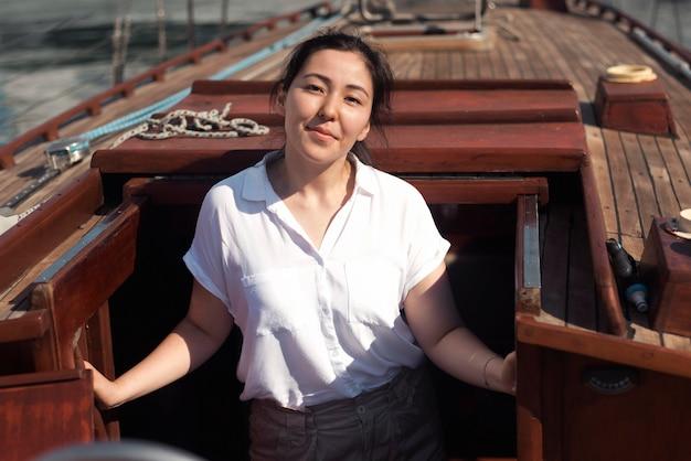 Mulher com vista frontal posando em um barco