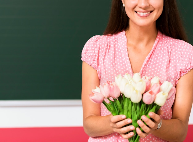 Mulher com vista frontal segurando um buquê de flores de seus alunos