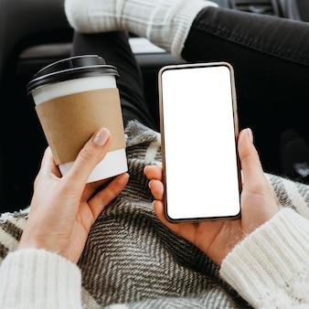 Mulher com vista frontal segurando um telefone em branco e uma xícara de café