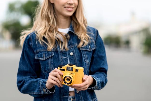 Mulher com vista frontal segurando uma câmera retro amarela