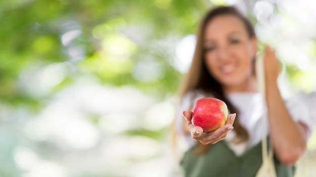 Mulher com vista frontal segurando uma maçã com espaço de cópia