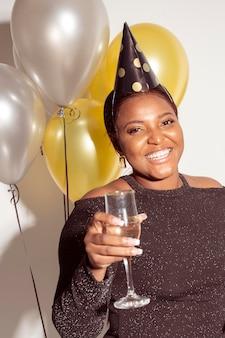 Mulher com vista frontal segurando uma taça de champanhe