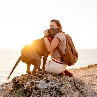 Mulher com vista lateral abraçando o cachorro ao pôr do sol