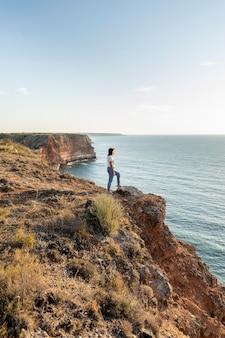 Mulher com vista lateral apreciando a vista em uma costa