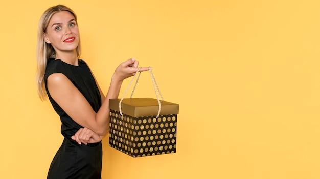 Mulher com vista lateral carregando uma grande caixa de presente