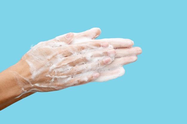 Mulher com vista lateral lavando as mãos sobre fundo azul